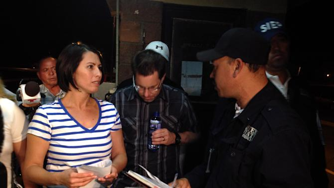 Yanira Maldonado, 42, left, accompanied by her husband, Gary, center, speaks to an official after being released from a prison on the outskirts of Nogales, Mexico late Thursday, May 30, 2013. Maldonado, jailed in Mexico on a drug-smuggling charge, was released after court officials reviewed her case. She was arrested by the Mexican military last week after they found nearly 12 pounds (5.4 kilograms) of pot under her seat on the commercial bus traveling from Mexico to Arizona. (AP Photo/Cristina Silva)