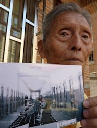 Chou Ching-feng holds an undated photo of a prisoner of war camp in Malaysia when Japan occupied Southeast Asia. Nearly 70 years ago, he worked for the Japanese army in what is now Malaysia, guarding Australian prisoners in one of the numerous POW camps in Southeast Asia