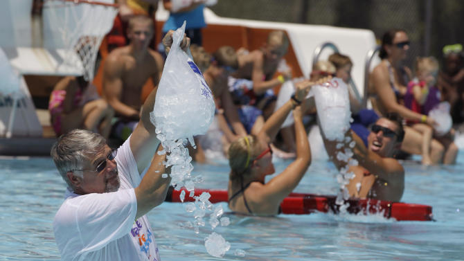 Franklin Mayor Fred Paris pours one of the 250 bags of ice into the Franklin Memorial Swimming Pool in Franklin, Ind., Thursday, July 21, 2011. Temperatures are expected to climb into the high 90's with heat index well over 100. (AP Photo/Darron Cummings)