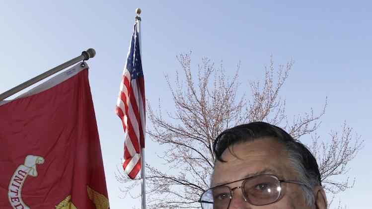 Marine veteran Harry Prestanski, 65, poses outside his home next to U.S. Marine Corps flag, Thursday, March 28, 2013, in West Chester, Ohio. Prestanski served 16 months as a Marine in the Vietnamese War and remembers having to celebrate his 21st birthday there. (AP Photo/Al Behrman)