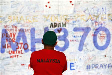 A man stands in front of a board with messages of hope and support for the passengers of the missing Malaysia Airlines MH370 at the departure hall of the Kuala Lumpur International