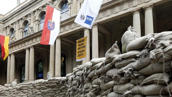 "Protesters have build a wall around the Frankfurt stock exchange with  sandbags to demonstrate against speculations in Frankfurt, central Germany, Sunday June 17, 2012. Poster in center reads: Transaction Tax  Now.   Activists calling for a tax on financial transactions have erected a wall of sandbags outside the Frankfurt stock exchange. The anti-globalization group Attac said that about 200 people participated in Sunday's action. Carrying placards with slogans such as ""Stem Speculation"" and ""Financial transaction tax now,"" they built the wall of sandbags around the statues of a bull and a bear symbols of optimistic and pessimistic markets  that stand in front of the exchange building.  Flags from left: teh German flag, the flag of Hesse State and the flag with the logo og teh Chamber of Commerce.  (AP Photo/dapd/Mario Vedder)"
