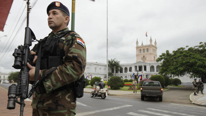 Soldiers stand guard outside the Presidential Palace, in Asuncion, Paraguay, Friday, June 22, 2012. Paraguayan lawmakers voted Thursday to impeach President Fernando Lugo for his role in a deadly clash involving landless farmers and police. Lugo's impeachment trial was to begin Friday in Paraguay's Senate. (AP Photo/Jorge Saenz)