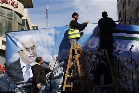 "Labourers put up a banner depicting Palestinian President Mahmoud Abbas before a rally in the West Bank city of Ramallah, supporting the resolution that would change the Palestinian Authority's United Nations observer status from ""entity"" to ""non-member state,"" November 29, 2012. The U.N. General Assembly is set to implicitly recognize a sovereign state of Palestine on Thursday despite threats by the United States and Israel to punish the Palestinian Authority by withholding much-needed funds for the West Bank government. REUTERS/Mohamad Torokman"