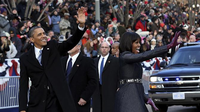 President Barack Obama and first lady Michelle Obama wave as they walk down Pennsylvania Avenue in Washington, Monday, Jan. 21, 2013, during the Inaugural Parade after his ceremonial swearing-in on Capitol Hill during the 57th Presidential Inauguration. (AP Photo/The New York Times, Doug Mills, Pool)