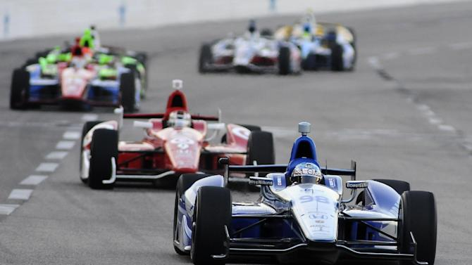 Pole-sitter Alex Tagliani (98) competes on the front stretch early in the IZOD IndyCar Firestone 550 auto race at Texas Motor Speedway, Saturday, June 9, 2012, in Fort Worth, Texas. (AP Photo/Ralph Lauer)