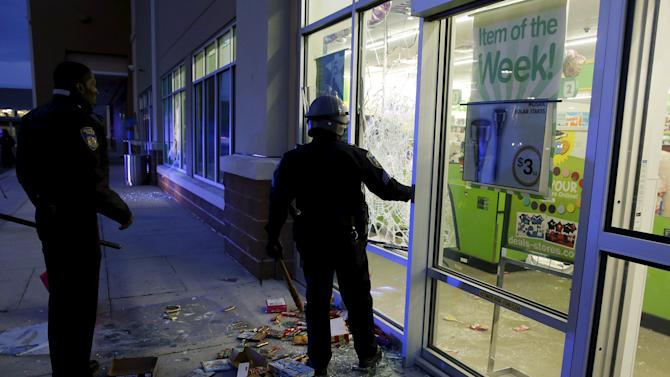 "Baltimore police officers arrive at a ""Deals"" store that was just vandalized and looted by rioters as darkness falls during clashes between rioters and police in Baltimore"