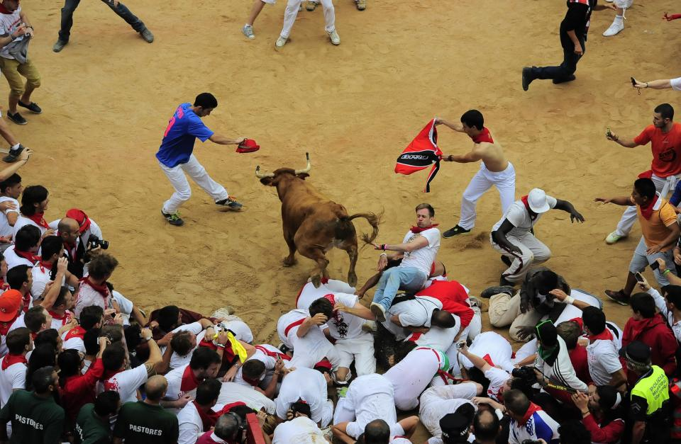 A bull jumps over revelers in the bull ring, at the end of third running of the bulls at the San Fermin fiestas, in Pamplona northern Spain, Monday, July 9, 2012. (AP Photo/Alvaro Barrientos)