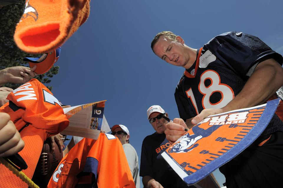 Denver Broncos quarterback Peyton Manning signs autographs for fans  following the opening session of Denver Broncos NFL football training camp in Englewood, Colo., Thursday, July 26, 2012. (AP Photo/Jack Dempsey)