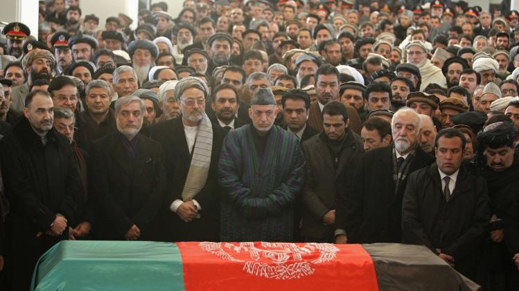 Afghan President Hamid Karzai prays near the flag-covered coffin of Afghan Vice-President Marshal Mohammad Qasim Fahim during his burial ceremony at the Presidential Palace in Kabul