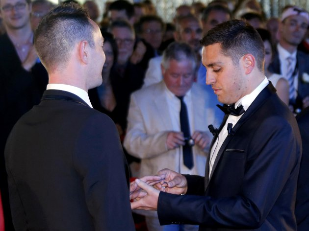 Bruno Boileau puts the ring on the finger of Vincent Autin as they are married at the town hall in Montpellier