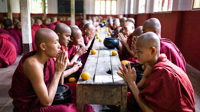 In this December 2012 photo monks pray before eating at the Buddhist Kaleywatawye Monastery in Yangon, Myanmar. (AP Photo/Richard Camp)