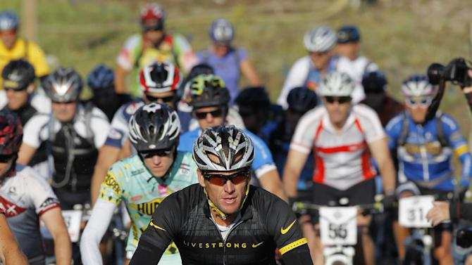 Lance Armstrong takes part in the Power of Four mountain bicycle race at the starting line in Snowmass Village, Colo., early Saturday, Aug. 25, 2012. The race is the first public appearance for Armstrong since the U.S. Anti-Doping Association stripped him of his seven Tour de France championships and banned him for life from the sport.  (AP Photo/David Zalubowski)