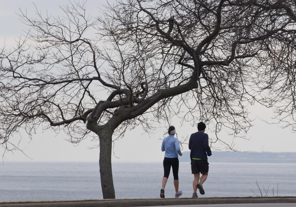 A pair of joggers enjoy the view of Lake Michigan Tuesday, Feb. 1, 2012, in Milwaukee. Temperatures have been above normal recently and most of the snow melted as the area experiences and unusual winter weather season. (AP Photo/Jeffrey Phelps)