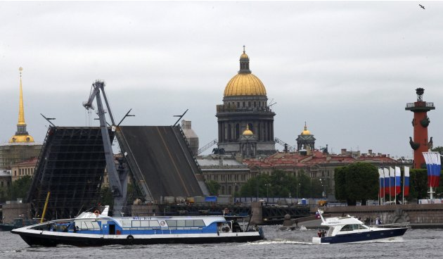 A yacht and a pleasure boat pass each other on the river Neva in front of the Palace Bridge and St. Isaac's Cathedral in St. Petersburg