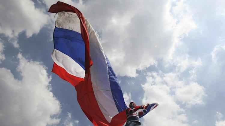 An anti-government protester waves a Thai national flag during a rally Saturday, May 10, 2014, in Bangkok, Thailand. The protesters achieved a partial victory on Wednesday when the Constitutional Court ousted Prime Minister Yingluck Shinawatra, saying she had violated the constitution by transferring a senior civil servant to benefit her politically powerful family. Nine other Cabinet members were also forced from their posts. (AP Photo/Sakchai Lalit)