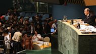 United Nations Secretary-General Ban Ki-moon (R) speaks before a vote on a UN General Assembly resolution on Syria at UN headquarters. He said the conflict has become a &quot;proxy war&quot; and that the international powers must overcome rivalries to end the violence