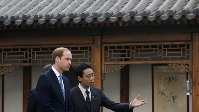 Britain's Prince William, Duke of Cambridge, is guided by Matthew Hu, China's representative of the Prince's School of Traditional Arts while he visits the Shijia Hutong in Beijing