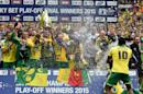 Norwich City striker Cameron Jerome (R) sprays champagne on his teammates as Russell Martin (C) holds up the trophy after Norwich City won the English Championship play-off final football match on May 25, 2015