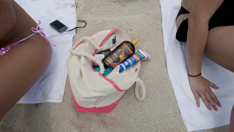 "In this Wednesday, May 9, 2012 photo, Morgan Weese, left, and Brittany Locke carry a supply of sun tanning products in their bag as they sun bathe in Miami Beach, Fla. Weese said she used to ""obsessed"" with tanning during high school, but now knows the dangers associated with tanning too much - including skin cancer. (AP Photo/J Pat Carter)"
