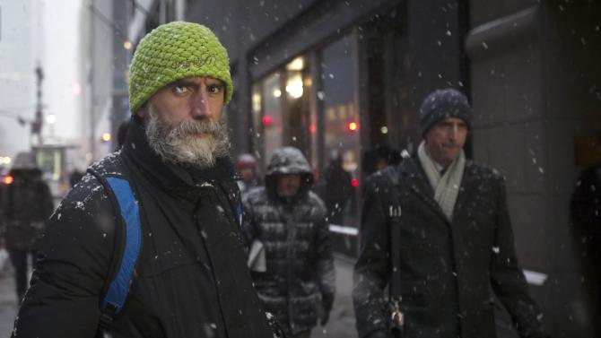 People walk along 42nd St at Grand Central Terminal as it snows in the Manhattan borough of New York