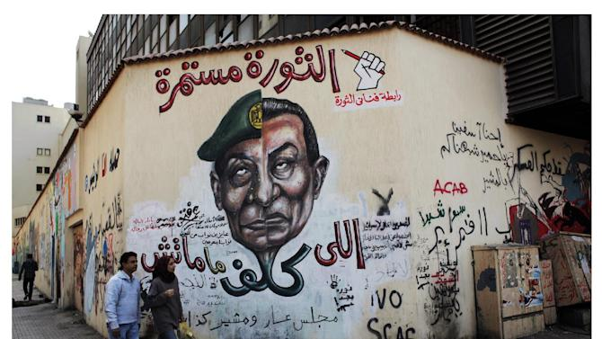 """FILE - In this file combo image of two photos taken in the same location; on March 22, 2012, above, an Egyptian couple walks by a mural depicting military ruler Field Marshal Hussein Tantawi on the left side of the face and ousted president Mubarak, right side with Arabic that reads, """"who assigned you did not die, No for gas export to Israel, the revolution continues"""", top;  a veiled Egyptian woman walks past a wall that was newly whitewashed during a cleanup campaign to erase old murals, in Tahrir Square, Cairo, Egypt, Wednesday, Sept. 19, 2012. Graffiti has been among the most powerful art forms and tools of Egypt's revolution and the turbulent months since, but it also has proven to be its most vulnerable and ephemeral. So a group of artists, photographers and a publisher joined hands to preserve the images. """"Wall Talk"""" _ their newly released, 680-page book _ collects hundreds of photos of graffiti dating from the Jan. 25, 2011 eruption of the revolt against then-President Hosni Mubarak until today.(AP Photo/Nasser Nasser, File)"""