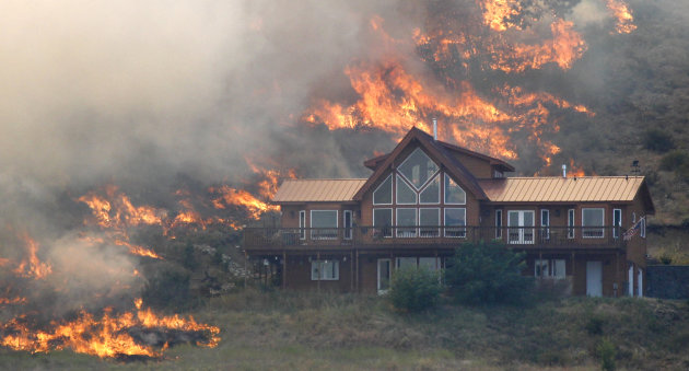 In this photo taken Tuesday, Aug. 14, 2012, flames surround a house on a hillside above Bettas Road near Cle Elum, Wash. A spokesman for the Washington state Department of Natural Resources said the house survived the fire because of the defensible space around the structure with the placement of the driveway and the lack of trees and brush up against the house, preventing flames from reaching it. Firefighters are still working to control the Bridge Taylor Fire and said that it&#39;s 25 percent contained. (AP Photo/Elaine Thompson)
