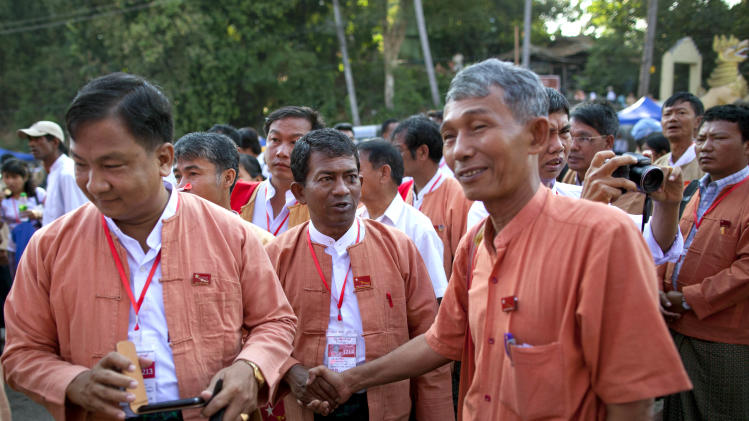 "Representatives of Aung San Suu Kyi's National League for Democracy shake hands outside the venue of first ever NLD party congress in Yangon, Myanmar, Friday, March 8, 2013. Nearly 900 representatives from across the country stood in neat lines outside the Taw Win (""Royal Rose"") restaurant, waiting to be screened for entry to elect their party leadership for the first time in the NLD's 25-year history. (AP Photo/Gemunu Amarasinghe)"