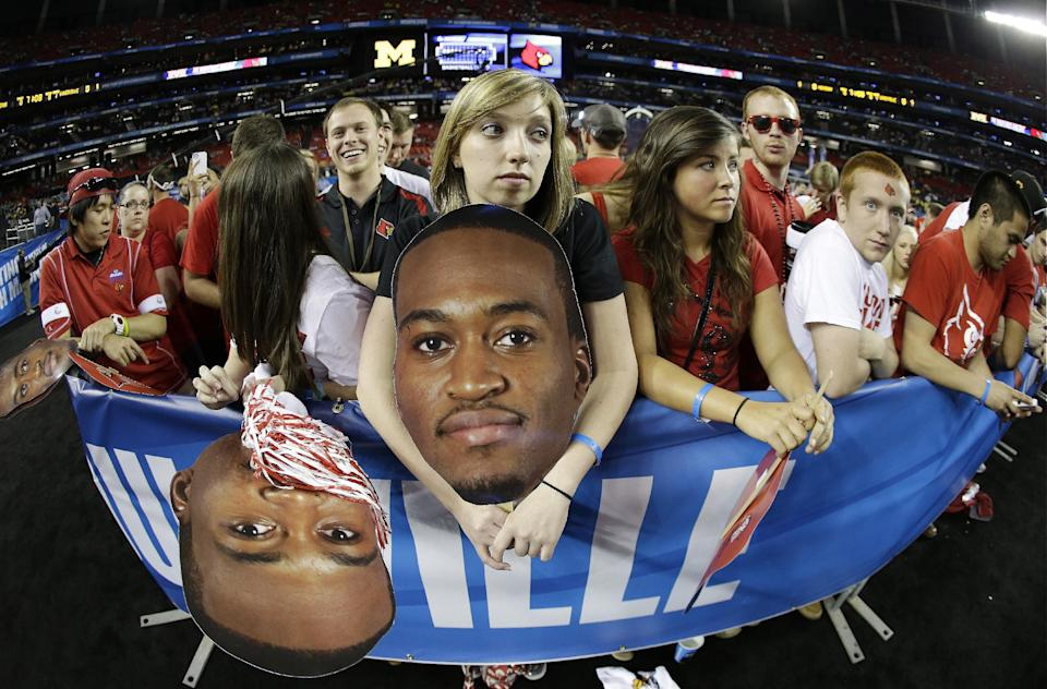 In this photo made with a fish-eye lens, Louisville fan Tara Pierce, 19, holds a over-sized photo of Louisville guard Kevin Ware before the first half of the NCAA Final Four tournament college basketball championship game Monday, April 8, 2013, in Atlanta. (AP Photo/John Bazemore)