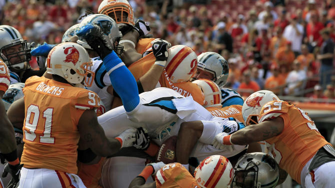 Carolina Panthers quarterback Cam Newton (1) dives over the Tampa Bay Buccaneers defense, including defensive end Da'Quan Bowers (91), middle linebacker Mason Foster (59) and strong safety Sean Jones (26), to score on a one-yard run during the first quarter of an NFL football game on Sunday, Dec. 4, 2011, in Tampa, Fla. (AP Photo/Chris O'Meara)