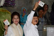 Incumbent Jakarta Governor Fauzi Bowo (R) and his wife Sri Hartati show their ballot papers before voting in the second round of Jakarta's gubernatorial election, on September 20. Voters in the Indonesian capital are casting their ballots in a run-off election for a new governor whose top challenges include tackling chaotic traffic jams and poor infrastructure