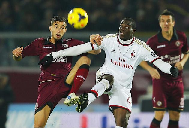 AC Milan's Mario Balotelli, right, and Livorno's Federico Ceccherini vie for the ball during a Serie A soccer match between Livorno and AC Milan in Leghorn, Italy, Saturday, Dec. 7, 2013