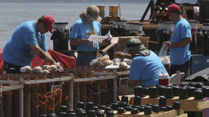 Pyro Spectaculars by Souza workers load shells into mortars on a barge docked in the Staten Island borough of New York, Saturday, June 29, 2013. Forty thousand shells are being loaded onto four barges in preparation for the Macy's Fourth of July fireworks display. (AP Photo/Mary Altaffer)
