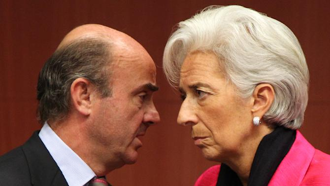 "International Monetary Fund managing director Christine Lagarde, right, talks with Spanish Economy Minister Luis de Guindos Jurado, during the Eurogroup finance ministers meeting in Brussels, Monday, Nov, 12, 2012. Greece's international lenders have prepared a ""positive"" report on the country's reform efforts, a crucial step in its efforts to secure the next installment of its bailout loan, the head the of group of finance ministers from the 17 euro countries said Monday. (AP Photo/Yves Logghe)"