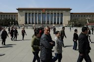 Chinese tourists walk past the Great Hall of the People which serves as the parliament building for the Communist Party of China. China's state media say the Communist Party has put on a forceful display of unity by expelling Bo Xilai but web users denounced the case as a sign of deep-rooted corruption plaguing the ruling party