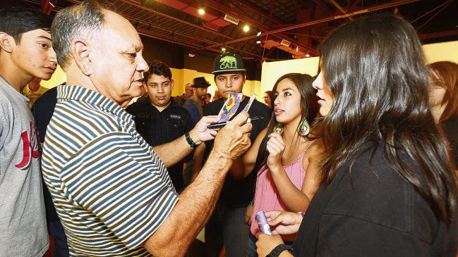 "Surrounded by Alma D'arte Charter School students, Cheech Marin looks at a student's artwork before the opening of his ""Chicanitas"" show Friday, May 2, 2014 in Las Cruces, N.M. The show features pieces from his Latino/Chicano art collection at the Las Cruces Museum of Art. (AP Photo/The Las Cruces Sun-News, Carlos Javier Sanchez )"