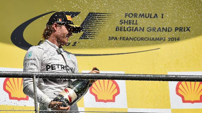 Mercedes-AMG's German driver Nico Rosberg celebrates on the podium at the Spa-Francorchamps circuit in Spa on August 24, 2014 after the Belgium Formula One Grand Prix