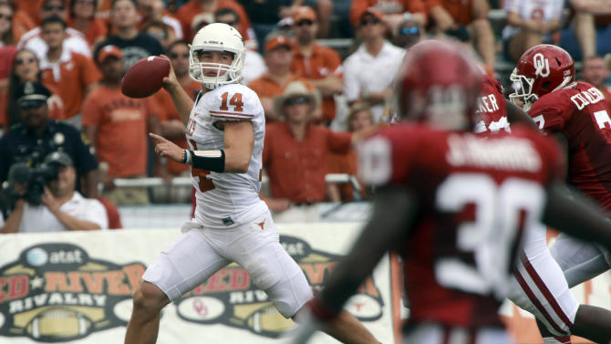 Texas quarterback David Ash (14) looks to pass as Oklahoma defenders close in during the first half of an NCAA college football game at the Cotton Bowl Saturday, Oct. 13, 2012, in Dallas. (AP Photo/Michael Mulvey)