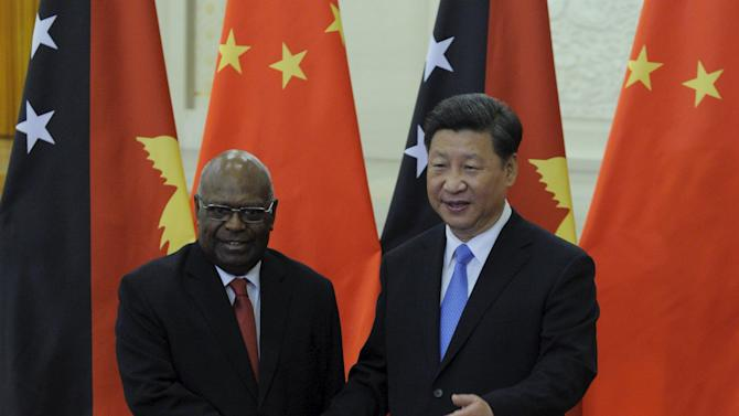 Chinese President Xi Jinping shakes hands with Papua New Guinea's Governor-General Michael Ogio before their meeting at the Great Hall of the People in Beijing