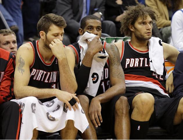 Portland Trail Blazers' Joel Freeland, left, LaMarcus Aldridge, center, and Robin Lopez, right, sit on the bench during the final minutes of their team's 120-109 loss to the Minnesota Timberwo