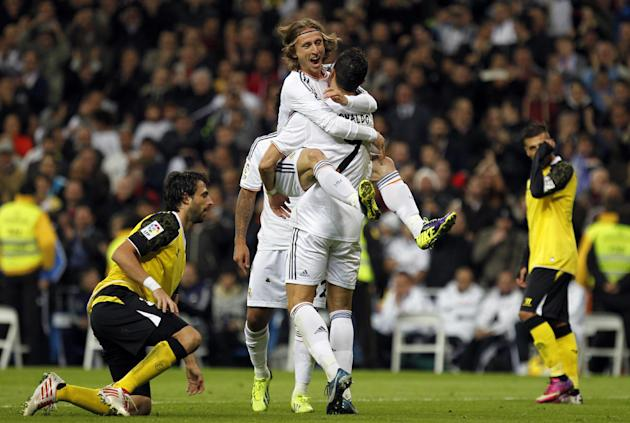 Real Madrid's Cristiano Ronaldo, centre right, from Portugal, celebrates with teammate Luka Modric from Croatia, top, after Ronaldo scored a goal against Sevilla during a Spanish La Liga soccer match