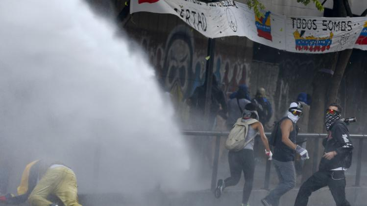 An anti-government protester is hit by water from a water cannon as another throws a molotov cocktail during riots in Caracas