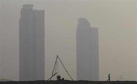 A man walks past a drilling well for terrene exploration in front of newly built residential buildings on a hazy day in Wuhan, Hubei province November 22, 2013. REUTERS/Stringer