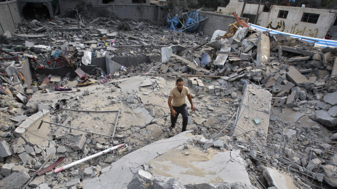 A Palestinian walks through the rubble of the house of Issam Al Da'slees, top aide of Hamas Prime Minister Ismail Haniyeh, after it  was hit by an Israeli air strike in Nuseirat Refugee Camp, central Gaza Strip, Wednesday, Nov. 21, 2012. (AP Photo/Adel Hana)