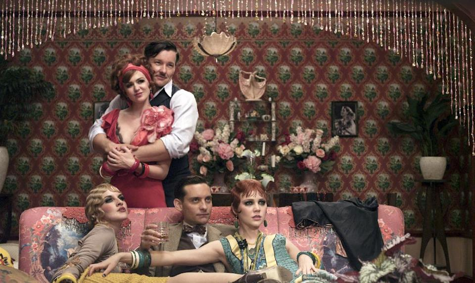 "This film publicity image released by Warner Bros. Pictures shows Isla Fisher as Myrtle Wilson, standing left, Joel Edgerton as Tom Buchanan, standing right, Adelaide Clemens as Catherine, seated from left, Tobey Maguire as Nick Carraway and Kate Mulvany as Mrs. McKee in a scene from ""The Great Gatsby."" (AP Photo/Warner Bros. Pictures)"