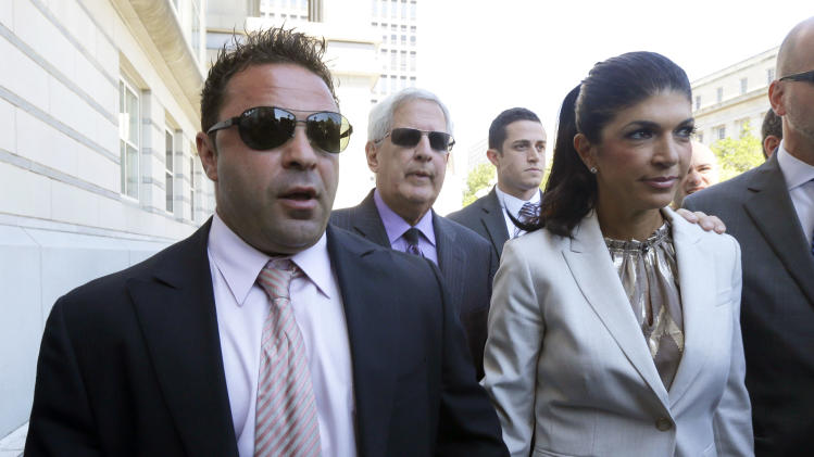 "FILE - In this July 30, 2013 file photo, ""The Real Housewives of New Jersey"" stars Giuseppe ""Joe"" Giudice, 43, left, and his wife, Teresa Giudice, 41, of Montville Township, N.J., walk out of Martin Luther King, Jr. Courthouse after an appearance in Newark, N.J. The couple is scheduled to enter a plea before a federal court judge Wednesday afternoon, Aug. 14, 2013. (AP Photo/Julio Cortez, File)"