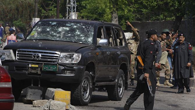 Pakistani troops gather next to a damaged vehicle which was used by a  paramilitary police commander at the site of a suicide bombing in Peshawar, Pakistan on Friday, March 29, 2013. A suicide bomber hits a security convoy carrying a paramilitary police commander in northwestern Pakistan, killing several people — including two women, but the commander escaped unhurt in the blast in Peshawar. Concerns are rising that the militants could step up the pace of attacks ahead of May parliamentary elections. (AP Photo/Mohammad Sajjad)