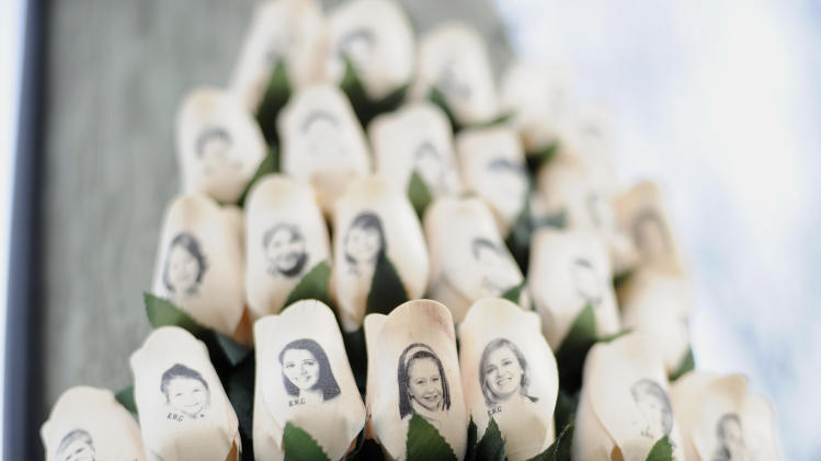 White roses with the faces of victims of the Sandy Hook Elementary School shooting are displayed on a telephone pole near the school on the one-month anniversary of the mass shooting that left 26 dead, including 20 children in Newtown, Conn., Monday, Jan. 14, 2013. (AP Photo/Jessica Hill)