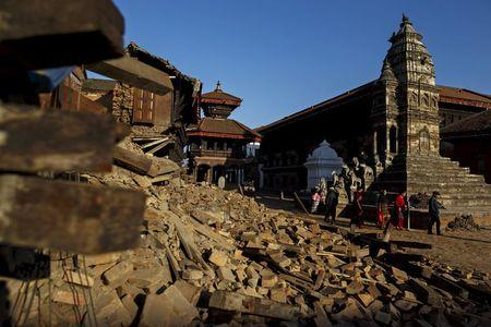 Local residents walk past the rubble from last week's earthquake in Bhaktapur, Nepal