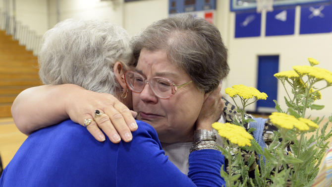 Martha Lloyd, right, hugs Karolyn Nunnallee following the memorial service for the 25th anniversary of the Carrolton bus crash at North Hardin High School May 14, 2013 in Radcliff, Ky. Lloyd was the 8th grade teacher of Nunnallee's daughter Patricia, one of the victims of the crash. (AP Photo/Timothy D. Easley)